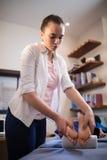 Ung kvinnlig terapeut som ger fotmassage till pojken som ligger på säng Fotografering för Bildbyråer