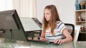 Ung kvinnlig tonåring som arbetar på en dator och typer en text stock video