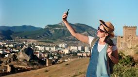 Ung kvinnlig turist för aktiv fotvandrare som tar selfie genom att använda smartphoneanseende på berget arkivfilmer