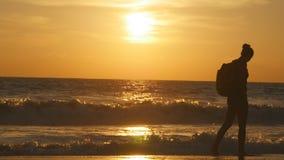 Ung kvinnlig turist med ryggsäcken som promenerar havsstranden på solnedgången Härlig ung handelsresandekvinna som går på havet lager videofilmer