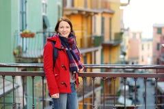 Ung kvinnlig turist som tycker om sikten av Manarola, en av de fem m?nghundra?riga byarna av Cinque Terre som lokaliseras p? kraf arkivbild