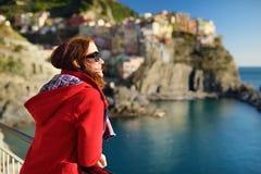 Ung kvinnlig turist som tycker om sikten av Manarola, en av de fem m?nghundra?riga byarna av Cinque Terre som lokaliseras p? kraf royaltyfri foto