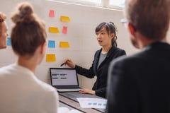 Ung kvinnlig utövande geende presentation till coworkers royaltyfri fotografi