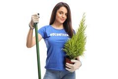 Ung kvinnlig volontär som rymmer en växt och en skyffel royaltyfri foto