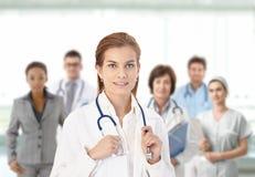Ung kvinnligdoktor framme av det medicinska laget Arkivfoton