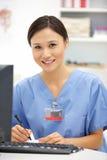 Ung kvinnligsjukhusdoktor på skrivbordet Royaltyfri Foto