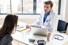 Ung läkare som lyssnar till hans patient med respekt och dedikation arkivfoton