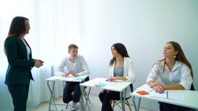 Ung lärare och studenter som har diskussion i klassrum stock video