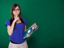 Ung lärare som frågar för tystnad på grön bakgrund Royaltyfria Bilder