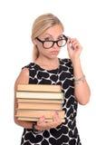 Ung lärarinna med exponeringsglas och böcker royaltyfria bilder