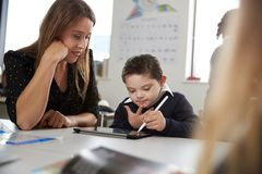 Ung lärarinna som arbetar med en Down Syndrome skolpojke som sitter på skrivbordet i ett grundskola för barn mellan 5 och 11 årkl royaltyfria bilder