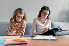 Ung lärarinna som ger privat kurs till barnet, liten flicka som sitter på hennes skrivbordhandstil i anteckningsbok arkivfoto