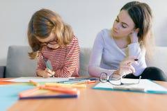 Ung lärarinna som ger privat kurs till barnet, liten flicka som sitter på hennes skrivbordhandstil i anteckningsbok royaltyfri bild