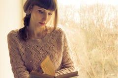 Ung läsebok för vuxen kvinna nära fönstret Arkivfoto