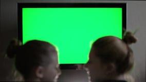 Ung långhårig blond seende grön TV för skärm två i aftonhemmiljö stock video