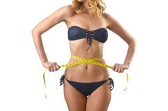 Ung lady med centimetr - begrepp för viktförlust Arkivbild