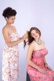 Ung latina flicka som kammar hennes hår och den Caucasian flickan fotografering för bildbyråer