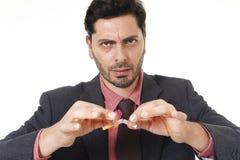Ung latinamerikansk attraktiv man som bryter cigaretten, i avslutat röka upplösning Royaltyfria Bilder