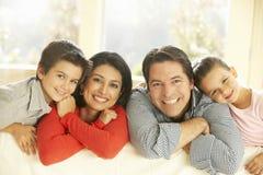 Ung latinamerikansk familj som kopplar av på Sofa At Home fotografering för bildbyråer