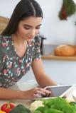 Ung latinamerikansk kvinna- eller studentmatlagning i kök Flicka som använder minnestavlan för att göra online-shopping eller för Arkivbild