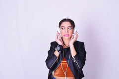 Ung latinamerikansk kvinna som lyssnar till musik med hörlurar Arkivbild