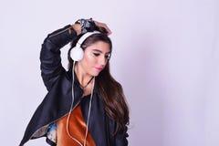 Ung latinamerikansk kvinna som lyssnar till musik med hörlurar Arkivbilder