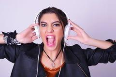 Ung latinamerikansk kvinna som lyssnar till musik med hörlurar Royaltyfria Foton
