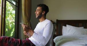 Ung latinamerikansk man som använder det lyckliga le Guy Chatting Online Over Big för minnestavladator fönstret med tropisk trädg lager videofilmer