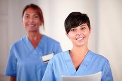 Ung latinamerikansk sjuksköterska rymma dokument royaltyfri bild