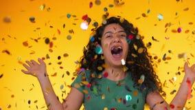 Ung latinsk flicka med dans för lockigt hår och hagyckel i konfettiregn på gul bakgrund Fira för kvinna arkivfilmer