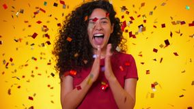 Ung latinsk flicka med dans för lockigt hår och hagyckel i konfettiregn på gul bakgrund Fira för kvinna stock video
