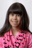 Ung latinsk flicka som ler med kulör hänglsen Fotografering för Bildbyråer