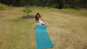 Ung latinsk kvinna som rullar ut yoga som är matt i parkera Arkivbilder