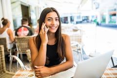 Ung latinsk kvinna som talar på telefonen med den öppna bärbara datorn i coffee shop fotografering för bildbyråer