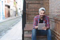 Ung latinsk man som använder en minnestavla arkivfoto