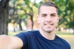 Ung latinsk man som tar en selfie i en parkera Arkivfoto