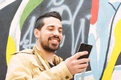 Ung latinsk man som tar selfie med minnestavlan arkivfoto