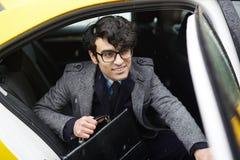 Ung le affärsman Leaving Taxi i regn royaltyfri foto