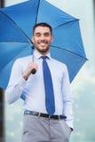 Ung le affärsman med paraplyet utomhus Arkivbild
