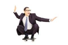 Ung le affärsman som rider en skateboard royaltyfri bild