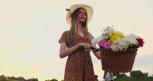 Ung le blondin i hatt och klänning som går i klänning med cykeln och blommor i korg stock video