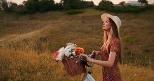 Ung le blondin i hatt och klänning som går i klänning med cykeln och blommor i korg lager videofilmer