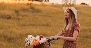Ung le blondin i hatt och klänning som går i klänning med cykeln och blommor i korg arkivfilmer