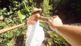 Ung le flicka för blandat lopp i den vita klänningen och Straw Hat Holding Hand och ledamannen till den fantastiska djungelvatten stock video