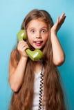 Ung le flicka med den gröna telefonluren Arkivbild