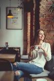 Ung le flicka med en kopp kaffe Fotografering för Bildbyråer