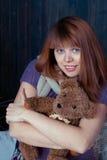 Ung le flicka med en nallebjörn Royaltyfri Foto