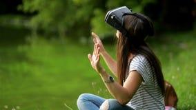 Ung le flicka med mörkt långt hår genom att använda mobila Apps med innovativt faktiskt teknologisammanträde nära sjön i stock video