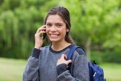 Ung le flicka som talar på ringa Fotografering för Bildbyråer