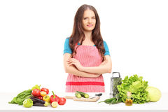 Ung le hemmafru med förklädet som förbereder sallad Arkivbild